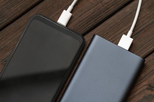 Смартфон заряжается от внешнего powerbank с помощью кабеля на коричневом деревянном столе.