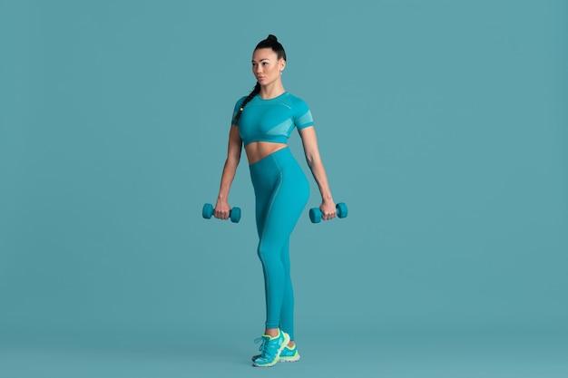 パワフル。スタジオで練習している美しい若い女性アスリート、モノクロの青いポートレート