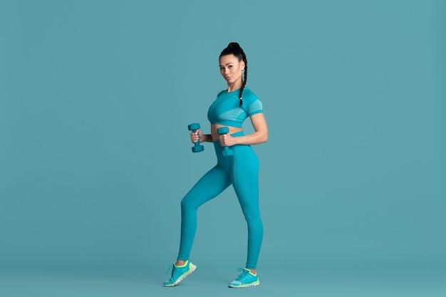 Мощный. красивая молодая спортсменка, практикующая в студии, монохромный синий портрет