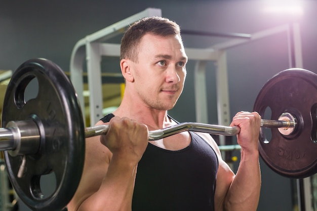 Powerful bodybuilder doing the exercises with barbell. strength and motivation.