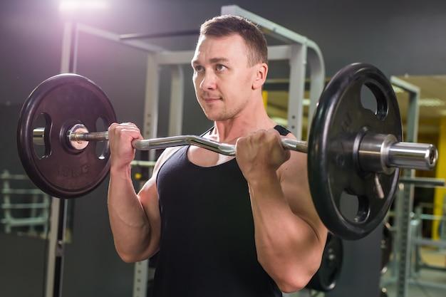 バーベルでエクササイズをしている強力なボディービルダー。暗い壁に裸の胴体を持つ強い男性の写真。強さとモチベーション。