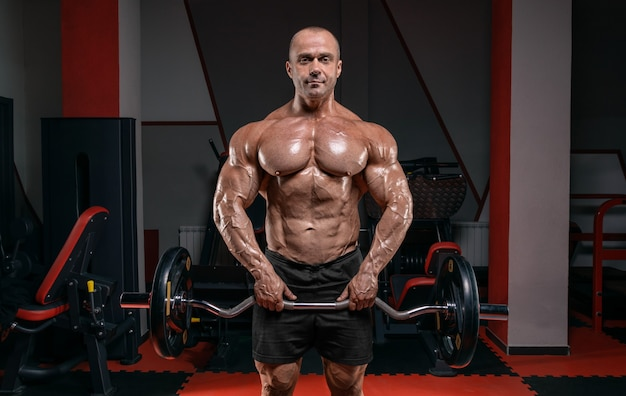 Powerful bodybuilder posing in the gym with a barbell. bodybuilding concept.