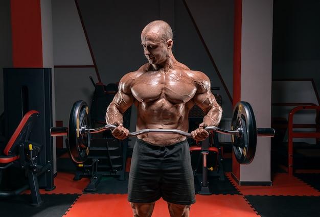 Мощный культурист позирует в тренажерном зале со штангой. концепция бодибилдинга. Premium Фотографии