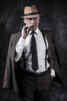 Powerful boss. serious senior man in hat and suspenders smoking cigar and looking at you while standing against dark background