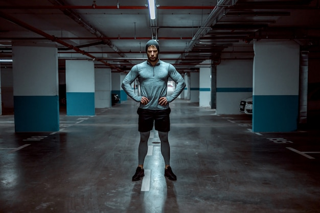 地下のガレージに立って腰に手を繋いでいる強力な白人フィットスポーツマン。成功は努力なしでは得られません。