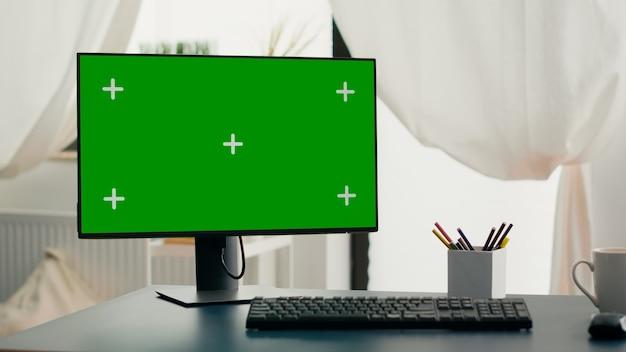 クロマキーの緑色の画面のモックアップを備えた強力なコンピューターが、リビングルームの机の上に立っています。誰もいないホームオフィスで隔離されたディスプレイを備えたpcはオンラインビジネス会議の準備ができています