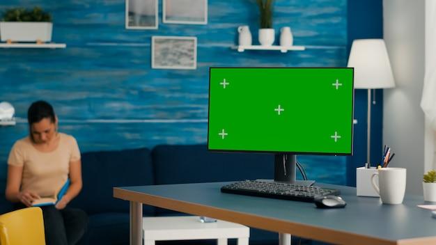 모의 녹색 화면 크로마 키가 있는 강력한 컴퓨터가 거실의 사무실 책상에 있습니다. pc 격리 디스플레이가 있는 밝은 방에서 배경으로 책을 읽는 여성