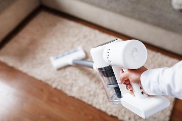 Мощный беспроводной пылесос с белой вихревой системой пылеулавливания чистит ковер в доме возле дивана.