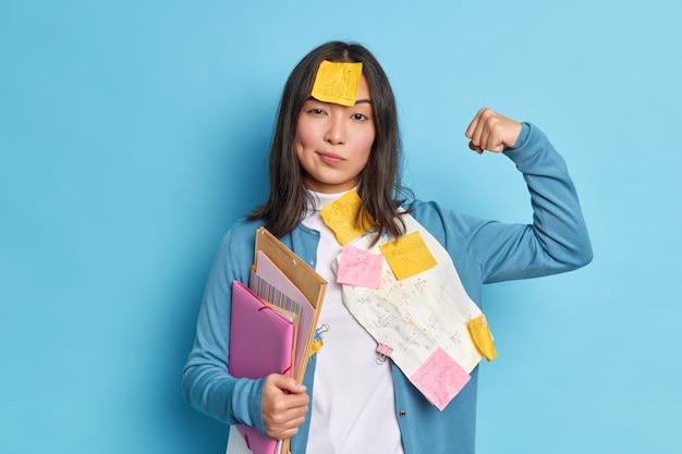 Сильная студентка поднимает руку и показывает мускулы, чувствует себя уверенно после работы над дипломной бумагой, носит наклейки на лбу, держит папки.