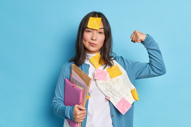 Powerful female student raises arm and shows muscles feels confident after working on diploma paper wears stickers on forehead holds folders.