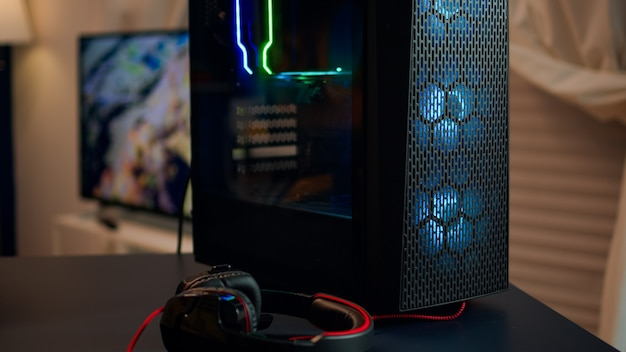 밤에 거실에서 게임 토너먼트를 위해 준비된 다채로운 rgb 조명이 있는 강력한 게임 장치. 사이버는 온라인 슈팅 게임을 하는 세련된 방에서 공연합니다.