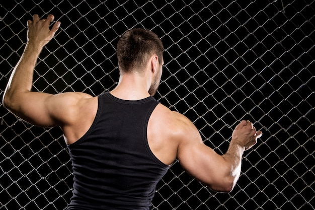 Powerful guy showing his muscles on fence