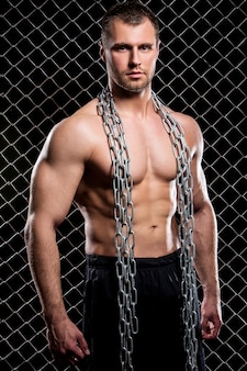 Powerful guy with a chain showing his muscles