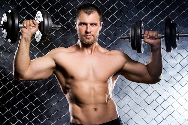 Powerful guy with a dumbbells showing muscles on fence