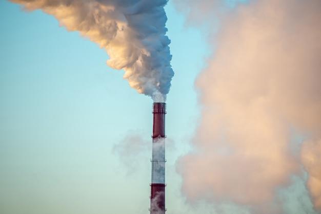 強力な工場の煙突が喫煙し、二酸化炭素を環境に放出しています