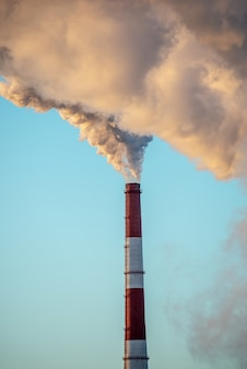 Powerful industrial factory chimney is smoking and emitting carbon dioxide into the environment
