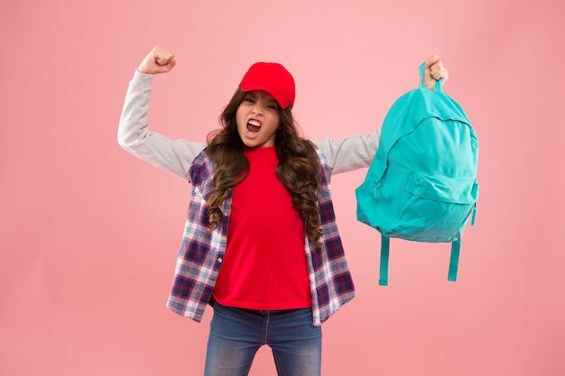強力な子供。バックパックで物を運ぶ。バックパックを正しくフィットさせる方法を学びましょう。女の子の小さなファッショナブルな子供はバックパックを運びます。便利なファッションアクセサリー。女子高生の赤い帽子の長い髪と学校のバックパック。