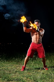 Powerful male boxer training outdoors at night