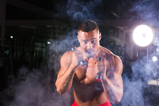 Powerful man doing boxing exercises, making direct hit with dumbbells.