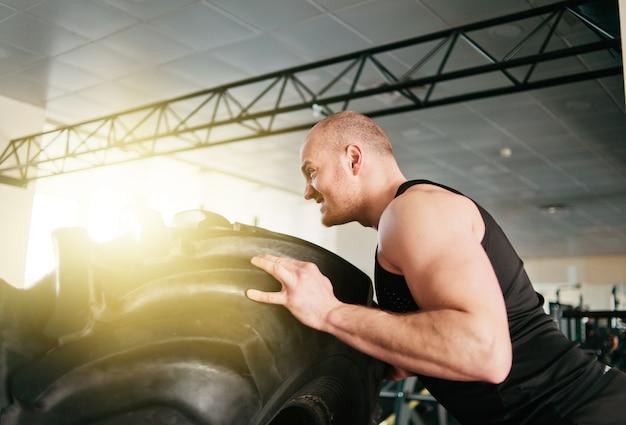 強力な男が大きな重いゴム製の車輪を押しています。ファンクショナルトレーニング
