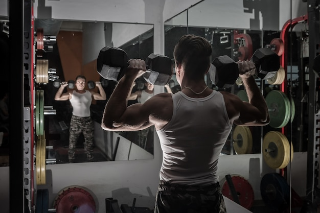 Powerful man lifting dumbbells near mirrors