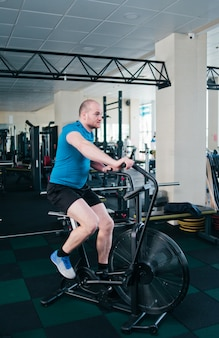 Powerful man trains with air bike. functional training concept