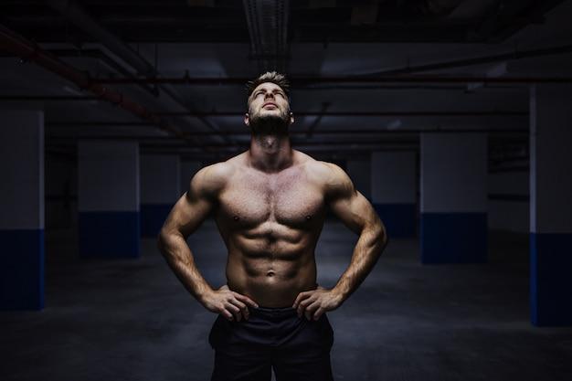 Мощный мускулистый спортсмен без рубашки, стоящий в гараже ночью с руками на бедрах и смотрящий вверх. городская жизнь.