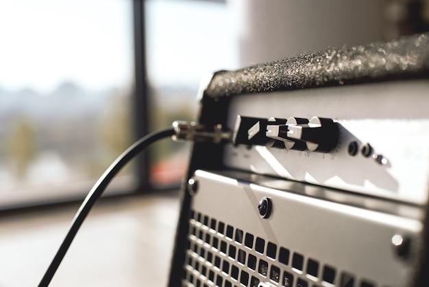Мощный звук вашей гитары. крупным планом вид гитарного усилителя с аудиоразъемом кабеля. музыкальные инструменты. музыкальное оборудование