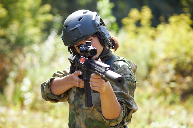 Powerful sportive woman soldier ready for battle wearing protective military gear weapon