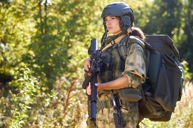 Powerful sportive woman soldier ready for battle wearing protective military