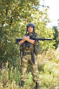 강력한 낚시를 좋아하는 여자 군인 보호 군사 장비 무기, 소총 또는 총을 착용하는 전투 준비. 야생의 자연 속에서