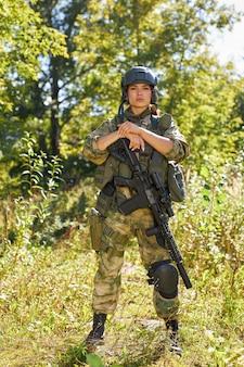 Мощная спортивная женщина-солдат готова к битве в защитном военном оружии