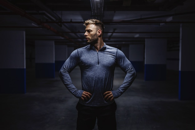 Powerful strong caucasian man in sportswear standing in garage with hands on hips and looking away. nighttime. urban life concept.