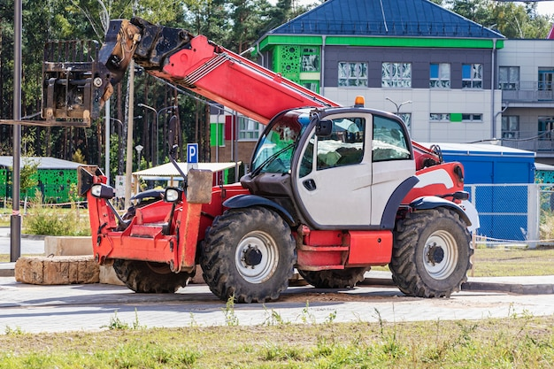 近代的な住宅地の建設現場にある伸縮マスト付きの強力なホイールフォークリフト。荷物を持ち上げたり移動したりするための建設機械。