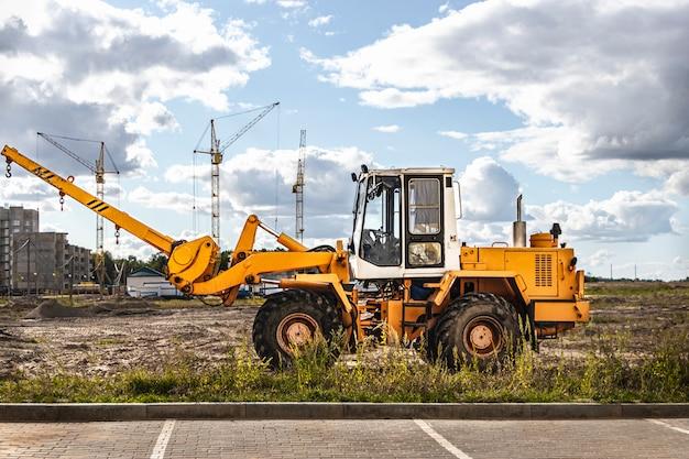 近代的な住宅地の建設現場でかさばる商品を輸送するための強力なホイールローダー。荷物を持ち上げたり移動したりするための建設機械。