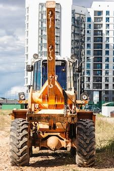현대 주거 지역의 건설 현장에서 부피가 큰 물건을 운반하는 강력한 휠 로더입니다. 짐을 들어 올리고 옮기는 건설 장비.