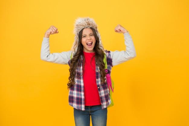 パワフル。学校での冬のイベント。冬の娯楽と活動。子供の女子高生の長い髪の柔らかい帽子は季節を楽しみます。冬のシーズンのコンセプト。子供の女の子は、イヤーフラップ付きの帽子をかぶっています。冬休み。
