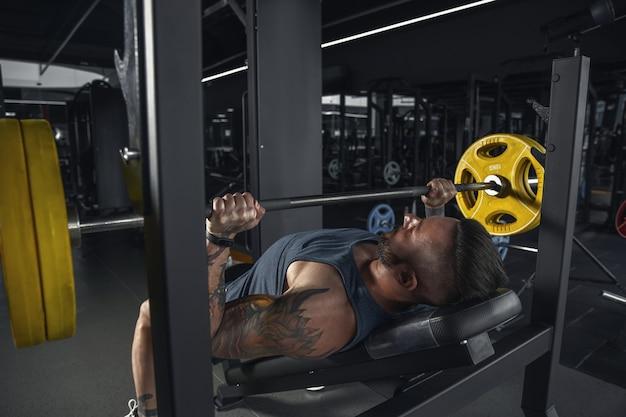 パワフル。ジムでバーベルを使ってプルアップを練習する若い筋肉質の白人アスリート。筋力トレーニングを行う男性モデル、上半身のトレーニング。健康、健康的なライフ スタイル、ボディービルのコンセプト。