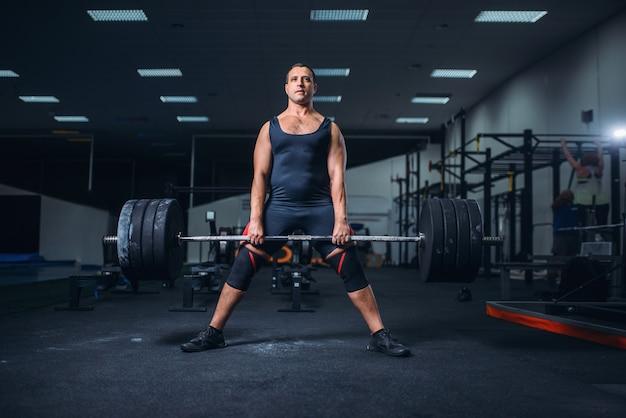 Пауэрлифтер держит вес тяжелой штанги