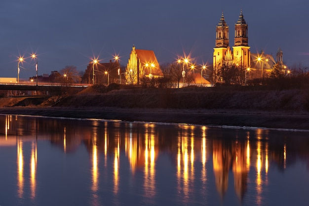 Poznan cathedral, archcathedral basilica of st peter and st paul at night with reflection in warta river, poznan, poland