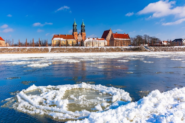 Poznan cathedral and ice drift on warta river in the winter sunny day, poznan, poland