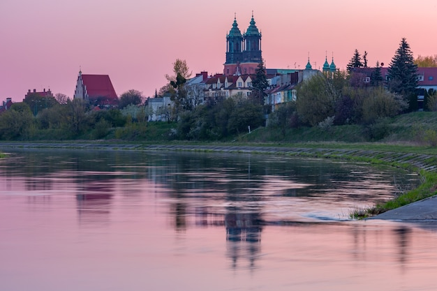 Poznan cathedral on the island of ostrow tumski and warta river at pink sunrise, poznan, poland.