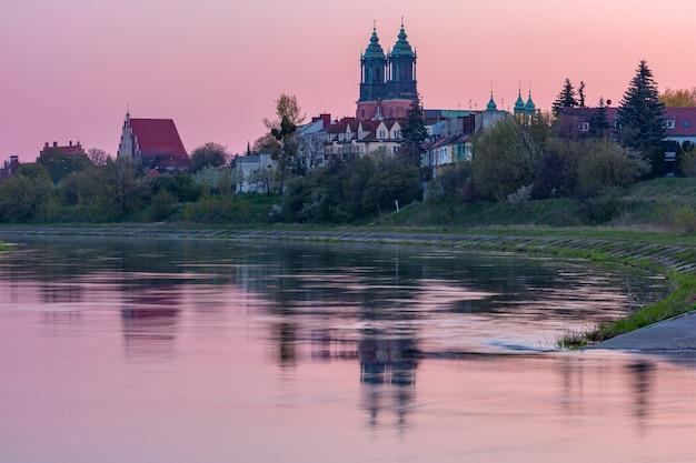 ポーランド、ポズナンのピンクの日の出にあるオストルフトゥムスキ島とヴァルタ川のポズナン大聖堂。