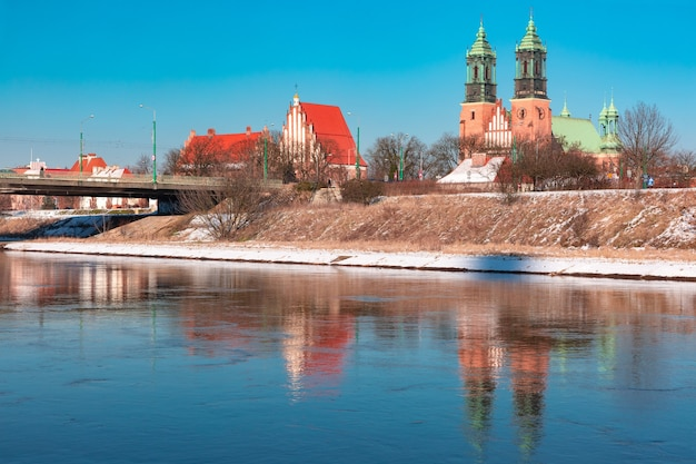 Poznan cathedral with reflection in warta river in the winter sunny day, poznan, poland