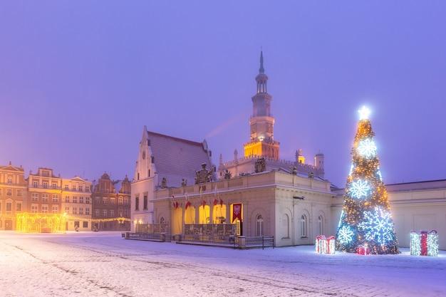 雪の降る夜、ポズナンの旧市街の旧市場広場にあるポズナン市庁舎とクリスマスツリー