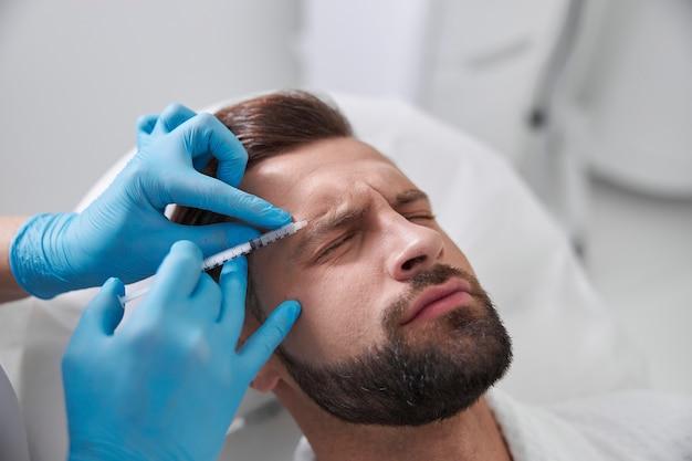 신중한 미용사가 이마에 리프팅 필러를 주입하는 동안 환자의 고통스러운 얼굴을 찡그린다