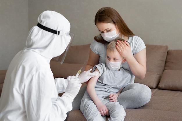 個人用防護服を着た医師またはppeがワクチンショットを注射して、コロナウイルス感染のリスクがある少年の免疫を刺激します。コロナウイルス、covid-19、ワクチン接種のコンセプト