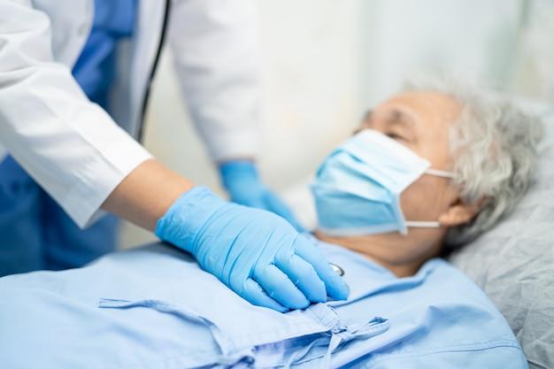 Ppeスーツと手袋を着用したアジア人医師が患者をチェックするためにcovid-19コロナウイルスを保護します。