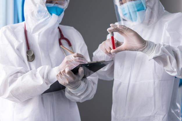 医師と看護師は病院でppeショーコロナまたはcovid-19血液チューブを着用し、フェイスマスクを着用しています。