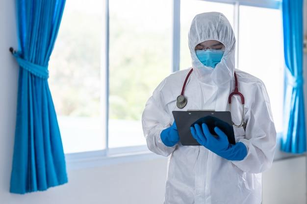 医師がppeを着用し、患者の医療記録をクリップボードに記録してコロナウイルスがないか確認する